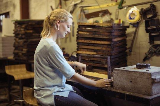 Female beekeeper preparing hive frame in factory