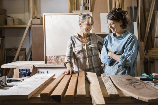 Two women choosing wood from a selection in a workshop