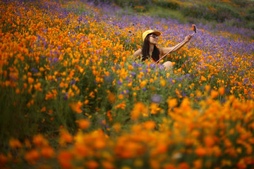 A woman uses a selfie stick to photograph herself in a massive spring wildflower bloom caused by a wet winter in Lake Elsinore