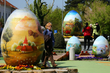 People walking between a two-metre-high Easter eggs painted in the traditional naive art style exhibition in Koprivnica