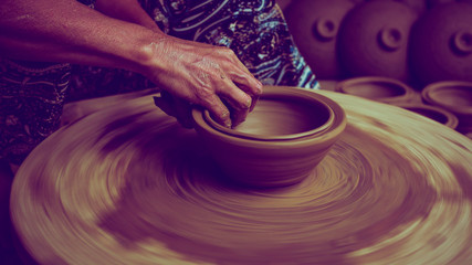 Potter's hands are making pot in pottery workshop