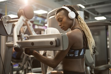 Young woman listening music while exercising on machine at gym