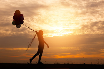 Silhouette woman with balloons in hand