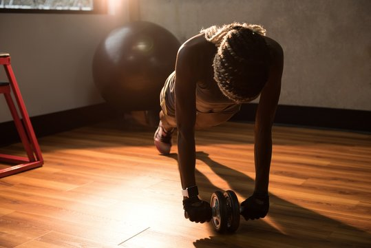 Woman exercising with ab roller wheel in the gym