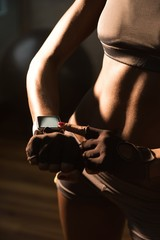 Mid-section of fit woman using smartwatch