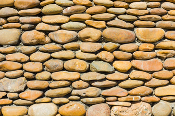 River pebbles round stone wall background