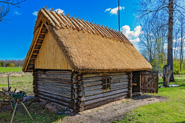 Old wooden sauna log cabin with thatched roof. Hiiumaa island, Estonia