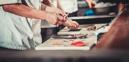 White chef in uniform prepare fresh fish fillet: eel, tuna, salmon. He is working on maki rolls. Preparing traditional japanese sushi set in interior of modern professional kitchen. Only hands closeup