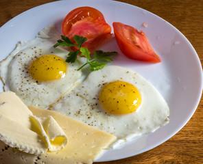 Яичница глазунья с помидорами, сыром и маслом