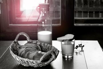 Бутылка и стакан с молоком на столе с хлебом