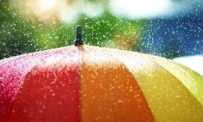 Rain drops falling onto umbella with rainbow colour- Rainy weather