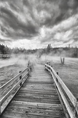 Black and white picture of a wooden bridge over steamy terrain in Yellowstone National Park, Wyoming, USA.