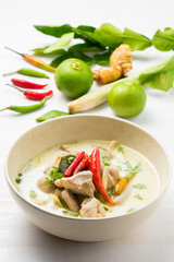 Thai chicken soup in coconut milk on white wooden background