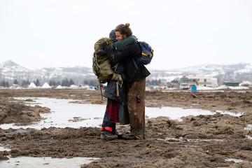 Susanna Travis, from Grass Valley, California, embraces Timothy Powers, also from California, before evacuating the main opposition camp against the Dakota Access oil pipeline near Cannon Ball