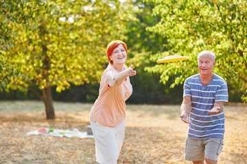 Senior couple playing frisbee and having fun