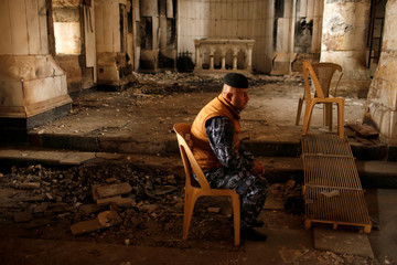 An Iraqi policeman attends the first Palm Sunday procession in the burnt out main church of the Christian city of Qaraqosh since Iraqi forces retook it from Islamic States militants,Iraq