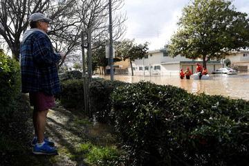 A man watches as firefighters extract residents stranded by the flood after in San Jose