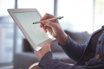 Woman using digital tablet while sitting at home