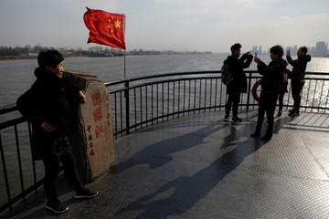 Tourists take pictures next to a Chinese flag on the Broken Bridge in Dandong