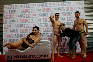 A visitor jokes with stripers as a transgender model poses on a couch at the Expo Sex and Eroticism adult exhibition in Mexico City, Mexico