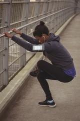 Young woman exercising on bridge