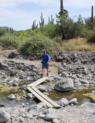 A Hiker Crosses Cave Creek, Spur Cross Ranch Conservation Area