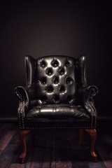 Black vintage leather armchair boss on a black background with wooden floor