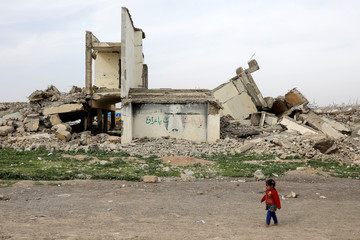 A displaced Iraqi child walks past debris outside Hammam al-Alil camp, south of Mosul