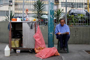 Jose Guillen poses for a picture next to his fruit juices street stall in Caracas
