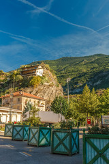 Travelling in Italian Alps - Little alpine town Susa Highly in mountains at hot shiny summer morning with blue cloudy sky