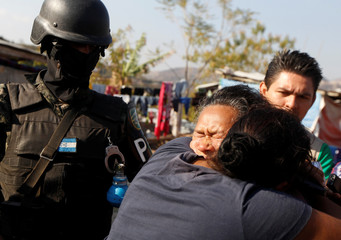 Members of the Military Police for Public Order (PMOP) arrested a woman as they search people for drugs and weapons during a patrol in the impoverished Villa Campesina neighbourhood in Tegucigalpa