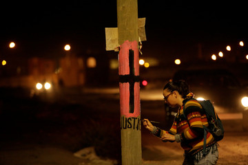 Activist paints the word 'Justice' on a lamp post under a black cross on a pink background to remember women who went missing or were killed, as they mark International Women's Day in Ciudad Juarez