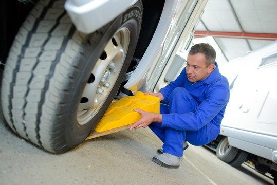 Man putting chock underneath wheel of campervan