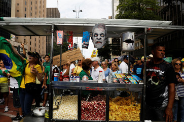 Man sells popcorn to demonstrators as he placed a mask with a defaced picture depicting Brazil's former president Lula da Silva on the cart at a protest in support of Lava Jato investigation in Sao Paulo