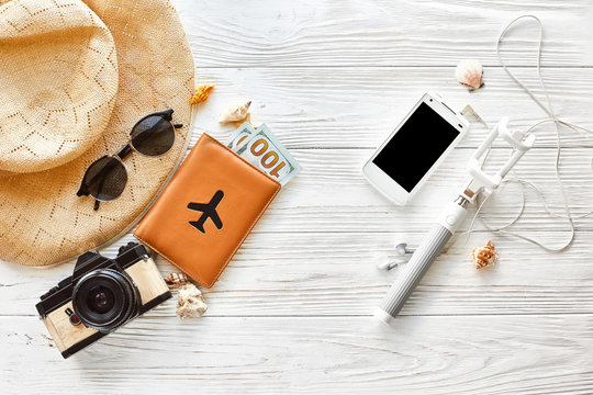 summer travel vacation concept flat lay, space for text. selfie stick phone camera passport money plane hat and sunglasses and shells on white wooden background top view. hello summer.