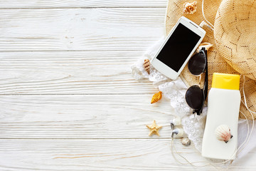 summer vacation concept flat lay. yellow hat, sunglasses phone sunscreen and shells  on white rustic wooden background, top view. space for text. travel and summer holiday
