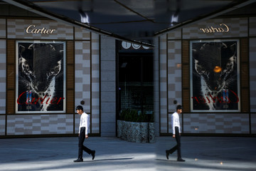 A man walks past a store of the luxury jeweller Cartier in Beijing