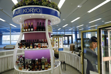 A vendor adjusts drinks at an Air Koryo bar at the airport in Pyongyang