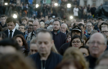 People observe a minute's silence at a vigil in Trafalgar Square the day after an attack, in London
