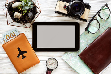 planning travel concept, space for text. tablet with empty screen, money map compass camera glasses wallet on white wooden background. time to travel wanderlust concept