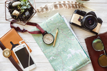 wanderlust and travel concept. compass and pencil on map exploring. passport money glasses photo camera on white wooden background. planning vacation. space for text. time to travel