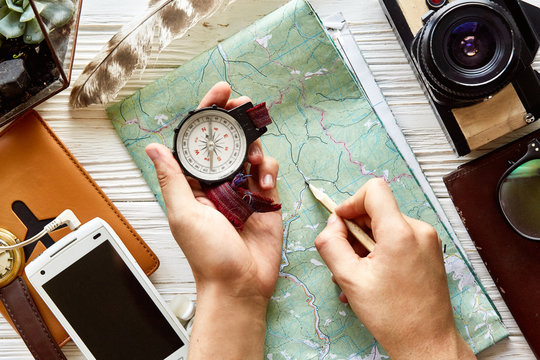 wanderlust and travel concept flat lay. hand holding compass and pencil on map exploring. passport money glasses photo camera  phone on white wooden background. planning vacation. space for text