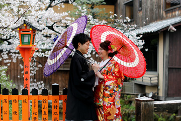 A couple chats while posing for a photo with blooming cherry blossoms in Kyoto