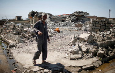A man walks past a building destroyed during the fighting between Iraqi forces and Islamic State militants in Gayyara