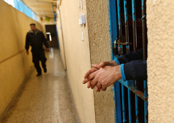 Drug addict stands behind the bar at a Hamas-run prison in Gaza City