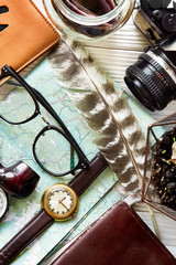 time to travel concept, hipster flat lay. map passport money compass and glasses pipe camera  feathers on white wooden background top view. planning vacation. space for text, wanderlust and explore