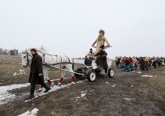 Revellers lead a cart with an effigy of Kostrubatyi Did, a symbol of winter, during the celebration of Maslenitsa also known as Kolodiy, a pagan holiday marking the end of winter, in Kiev, Ukraine