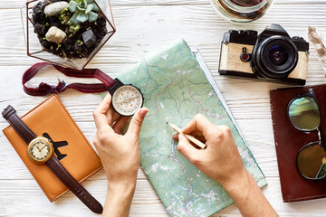 wanderlust and travel concept flat lay. hand holding compass and pencil on map exploring. passport money glasses photo camera on white wooden background. planning vacation. space for text
