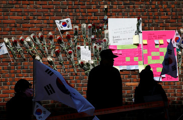 Supporters of South Korea's ousted leader Park Geun-hye are silhouetted in front of messages and flowers dedicated to Park outside her private home in Seoul