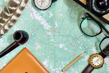 wanderlust and travel concept, hipster flat lay. map passport compass and glasses photo camera pipe on black wooden background top view. planning vacation. space for text